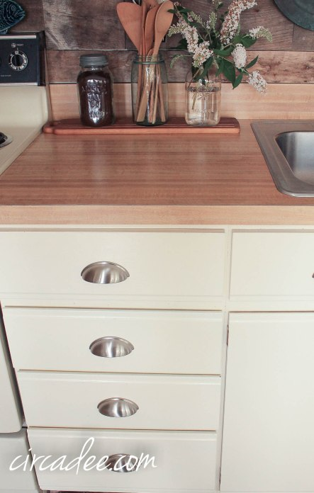 pallet wood back splash & painted laminate cabinets eith industrial pulls