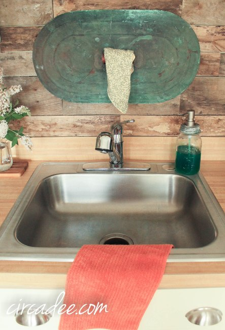 copper lid turned dish towel rack on pallet wood backsplash
